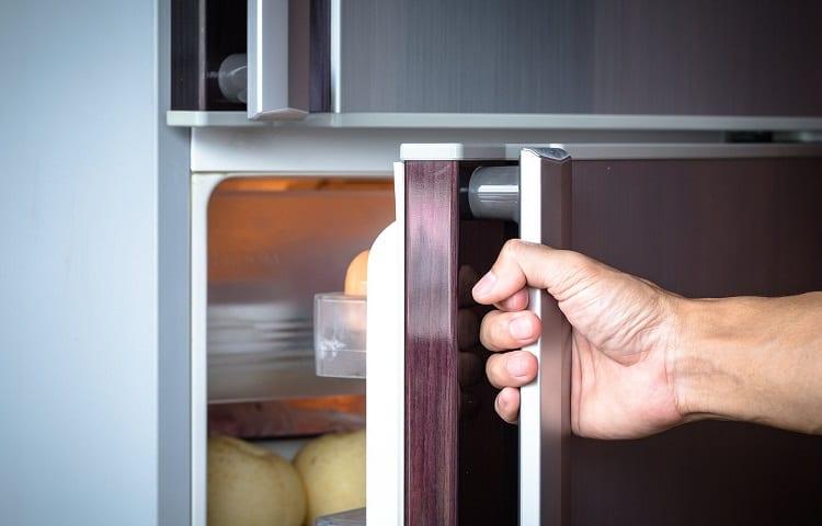 man is opening a refrigerator door