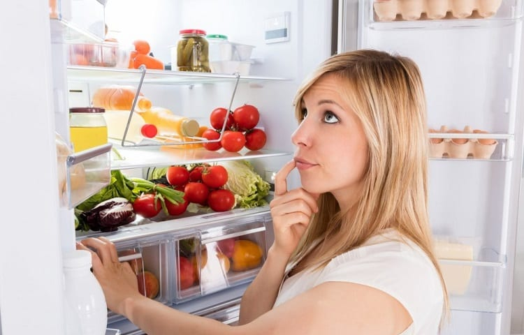 woman thinking in front of a fridge