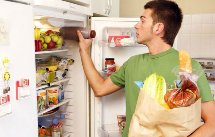 young man storing groceries in overpacked fridge