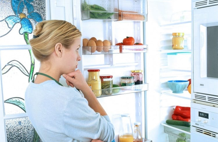 confused woman in front of the fridge
