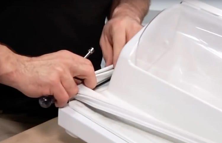 man changes seal on fridge door